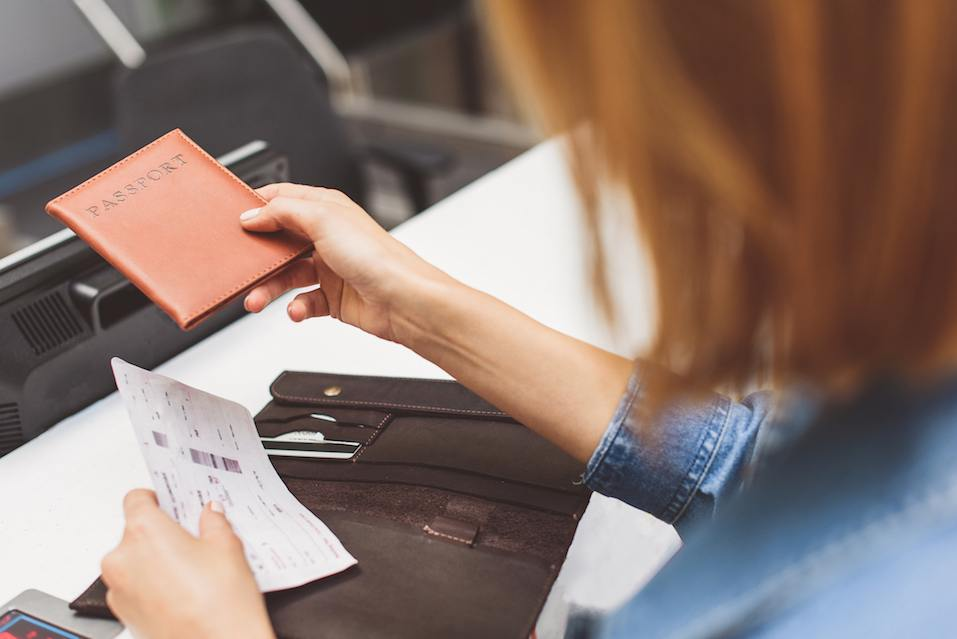 Young female passenger is giving her passport to check-in officer
