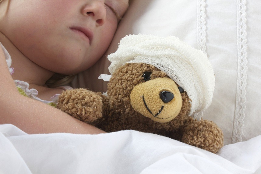 Young girl poorly in bad cuddling her teddy