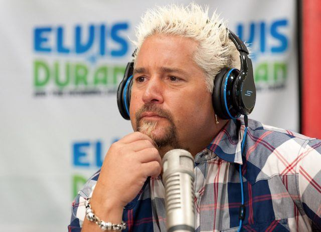 Guy Fieri wears a set of headphones and sits in front of a silver microphone.