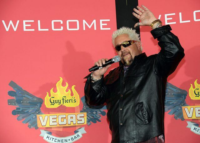Guy Fieri holding a microphone as he hosts an event for his brand.