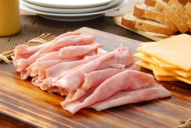 Deli meats laid out on a wooden board.