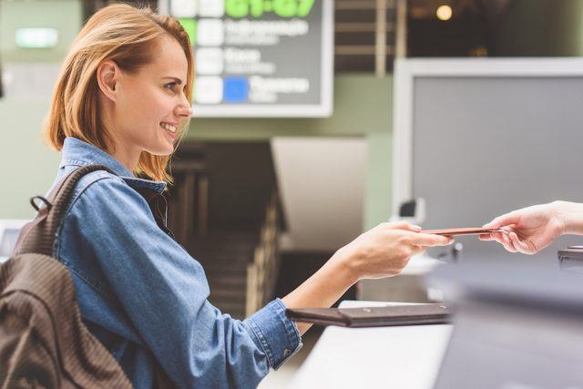 woman is showing her documents to check-in attendant
