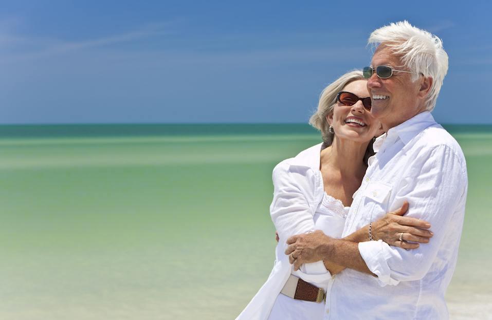 Happy senior couple in white on tropical beach