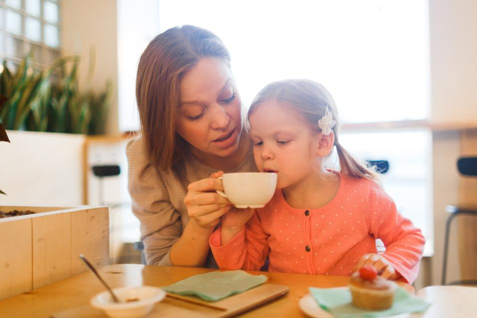 Young woman looking at her daughter drinking hot tea