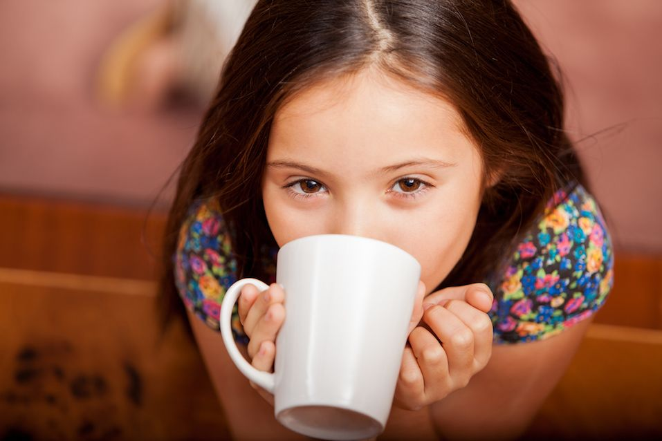 Happy little girl enjoying a cup of hot chocolate at home