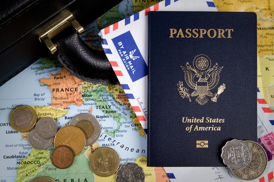USA passport, foreign coins and briefcase sit on a world map