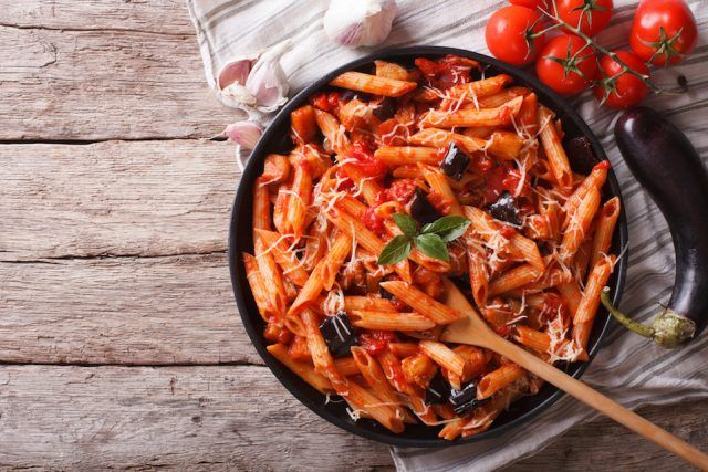 Italian pasta in a black pot with a wooden spoon.