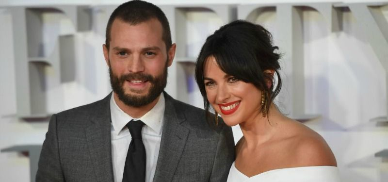 Jamie Dornan and Amelia Warner pose together on the red carpet.