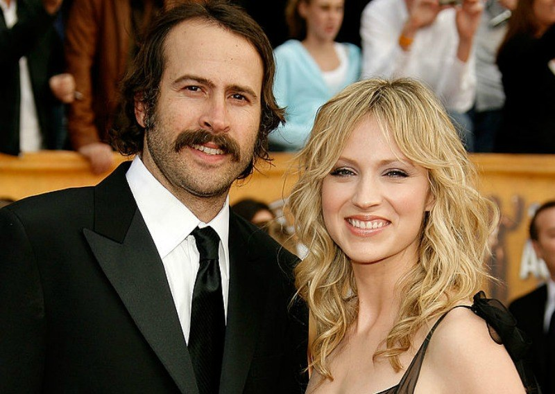 Jason Lee and Beth Riesgraf are smiling together on the red carpet.