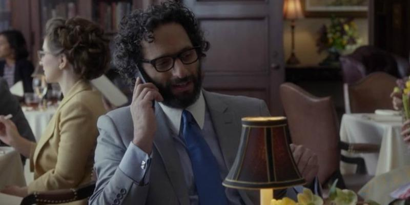 Jason Mantzoukas is in a suit and talking on a phone.