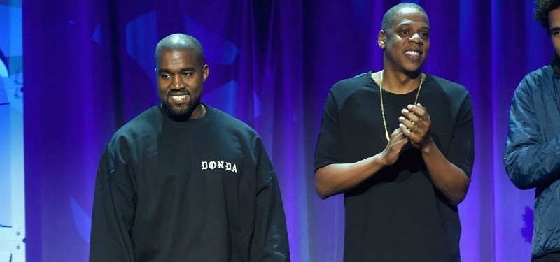 Jay Z is clapping and standing next to Kanye West.