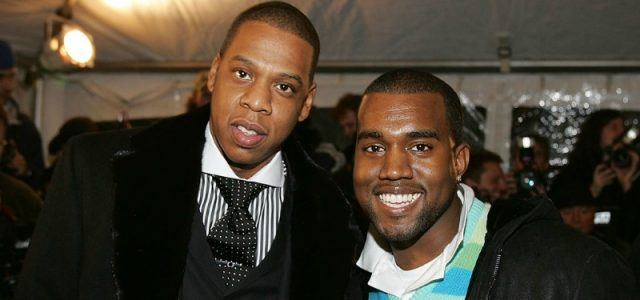 Jay-Z and Kanye West are smiling on the red carpet.