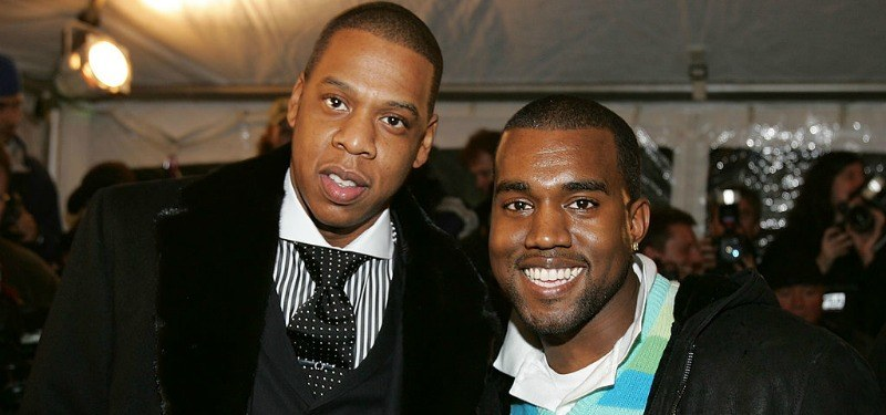Jay Z and Kanye West are smiling on the red carpet.