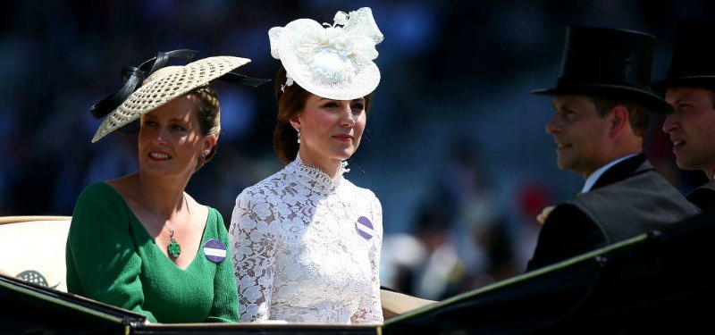 Kate Middleton is sitting in a carriage in a white lace dress and hat.