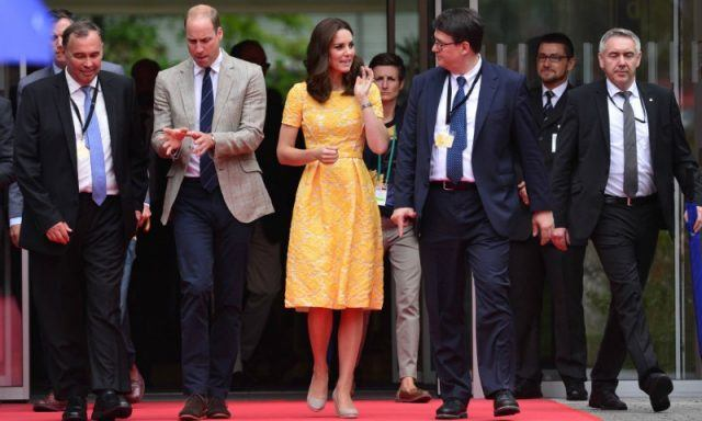 Kate Middleton and Prince William are walking alongside men in suits on a red carpet.