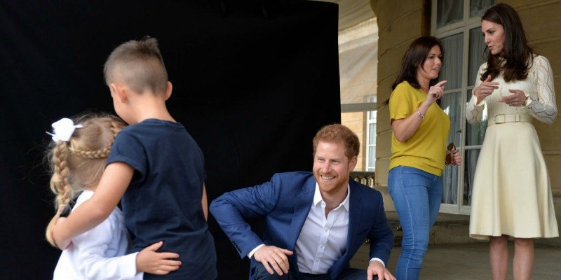 Kate Middleton is talking to a woman as Prince Harry watches two kids hug.