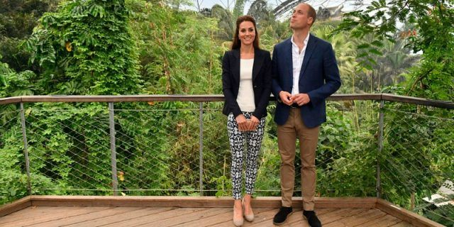 Kate Middleton is wearing a white shirt, dark blazer, and patterned pants while standing next to Prince William, who is looking stylish in brown pants and a dark blazer.