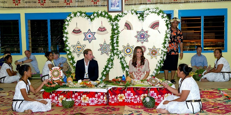 Kate Middleton and Prince William are sitting down in huge chairs at a dinner table as two woman sit down on the ground next to them.