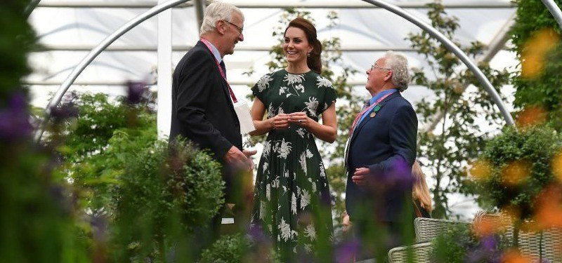 Kate Middleton is in a green floral dress and talking to two men in a greenhouse.