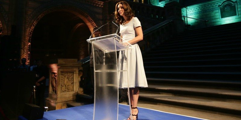 Kate Middleton is speaking in a light blue dress at a podium.