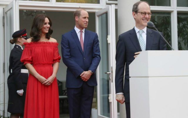 Kate Middleton is in a red strapless dress and is standing next to Prince William as an ambassador giving a speech.