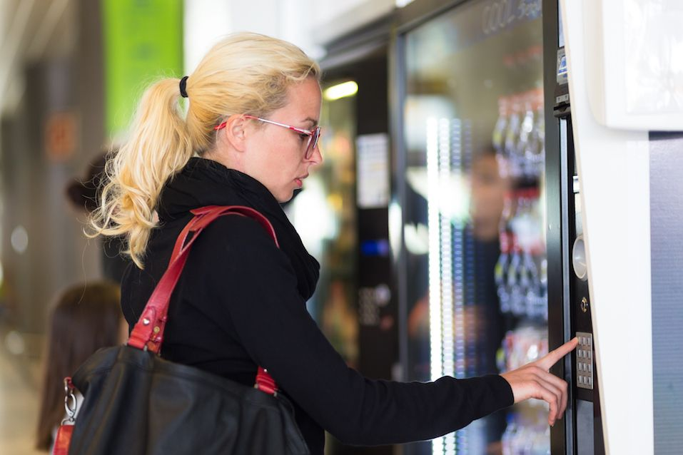 woman using a modern beverage vending machine