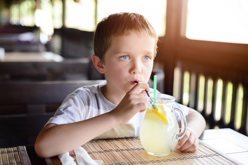 Little child boy enjoying his delicious lemonade