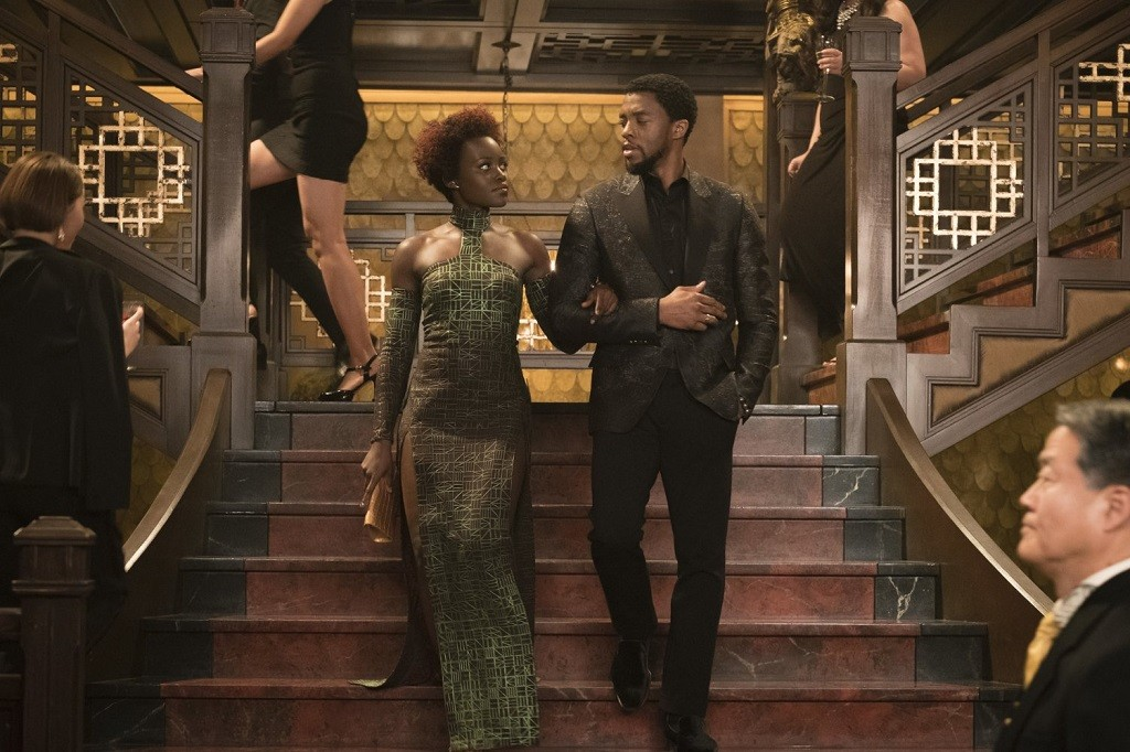 Lupita Nyong'o and Chadwick Boseman in formal wear descending a staircase.