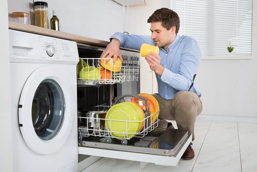 Man Arranging Dishes In Dishwasher