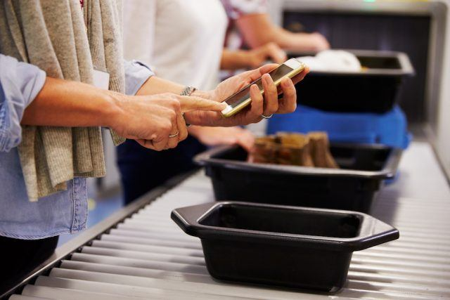 Man Checking Mobile Is Charged At Airport Security Check