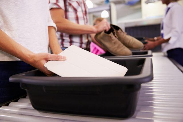 Man Puts Digital Tablet Into Tray For Airport Security Check