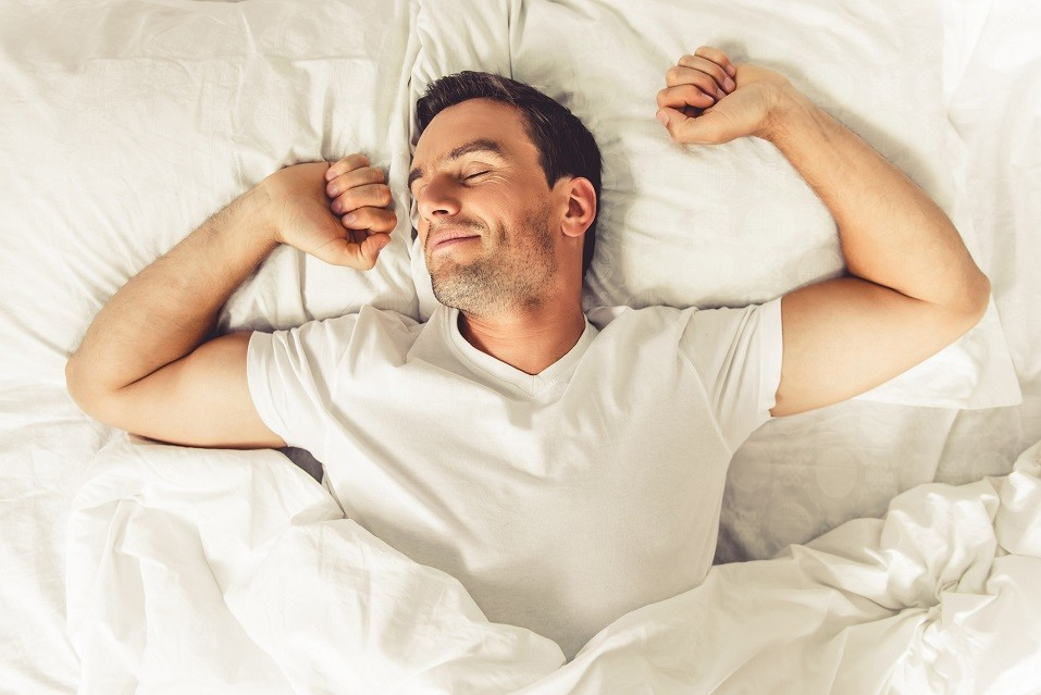 Handsome man smiling while sleeping in his bed at home