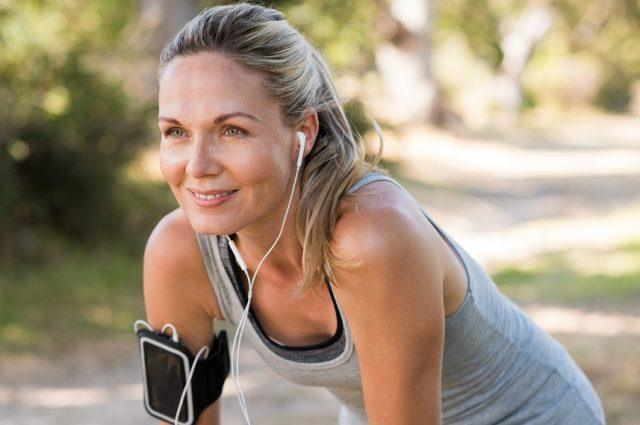 A woman takes a break from running while listening to music.