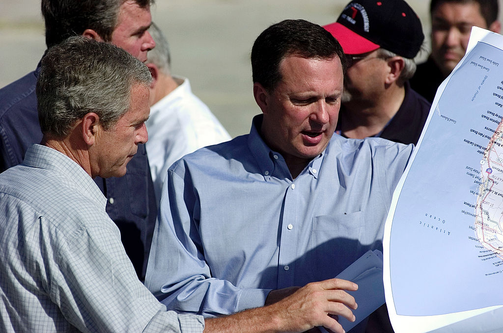 Michael Brown, a high-ranking FEMA official, shows then-President George W. Bush maps of Florida areas affected by Hurricane Charley.