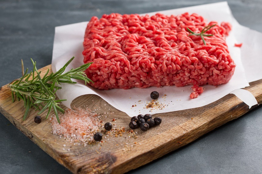 Minced red meat on butcher paper with basil
