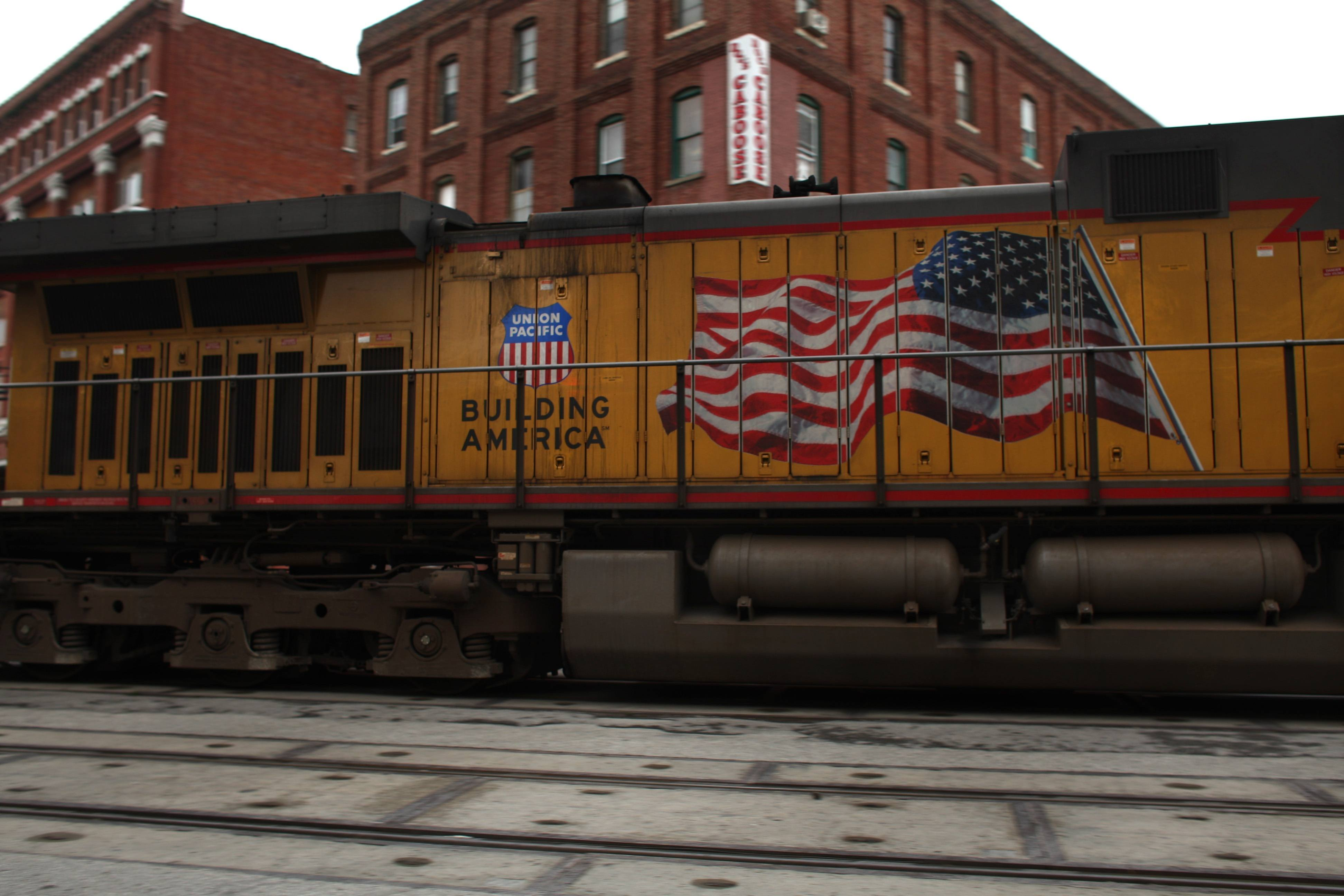 A train passes through an area of old warehouses in Kansas City