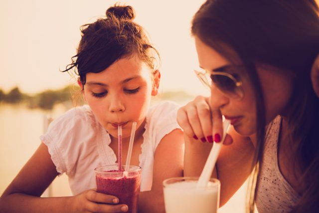 Mother and daughter drinking juice at a cafe