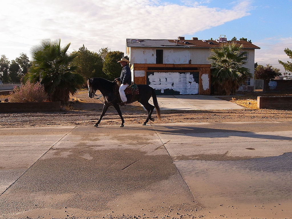 A man rides a horse by an abandoned home on in Las Vegas, Nevada