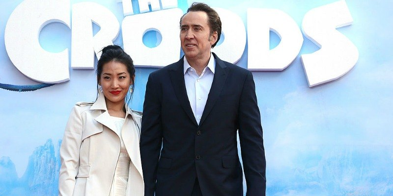 Alice Kim and Nicolas Cage pose together in front of a poster of The Croods.