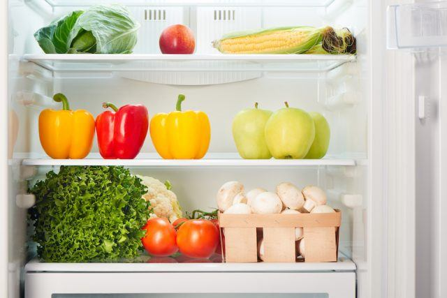 Open refrigerator full of fruits and vegetables.