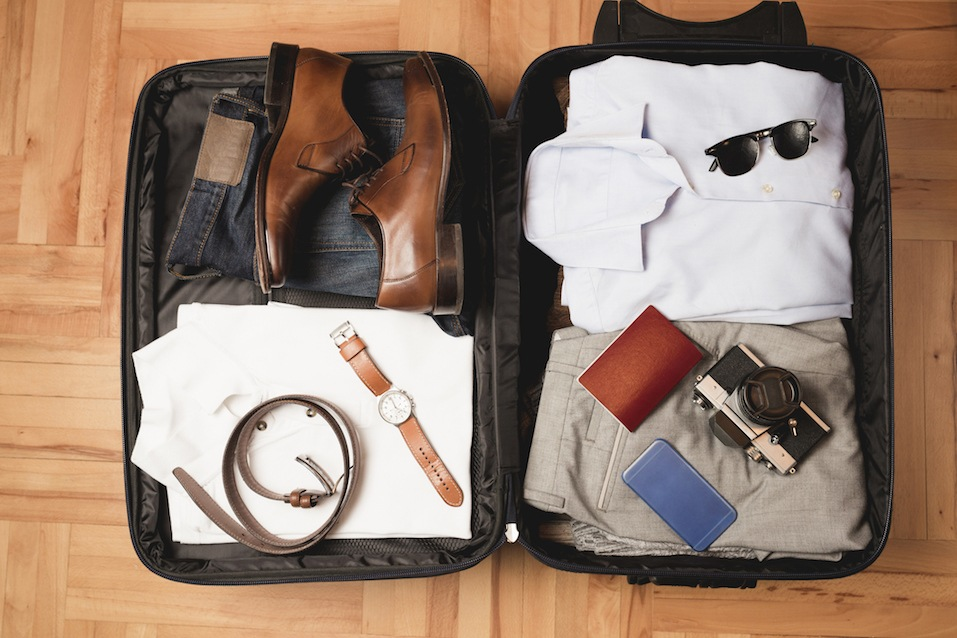 Open traveler's bag with men clothing and accessories