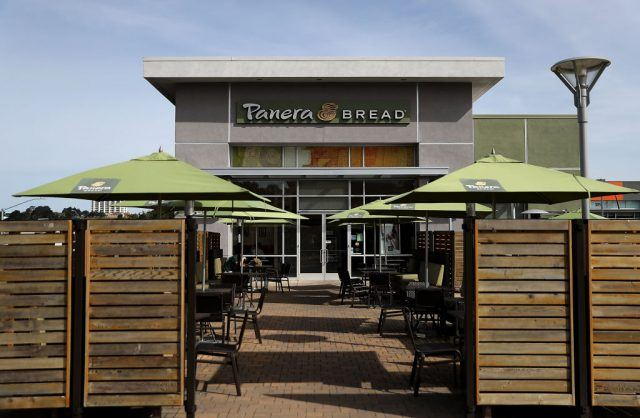 Front view of Panera Bread restaurant with tables and chairs out front