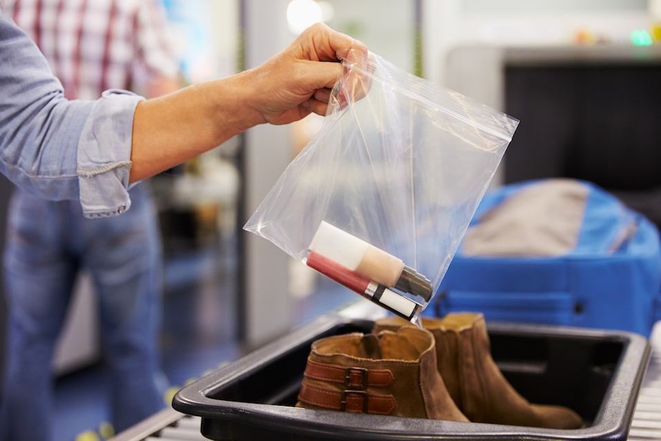 Passenger Puts Liquids Into Bag At Airport Security Check