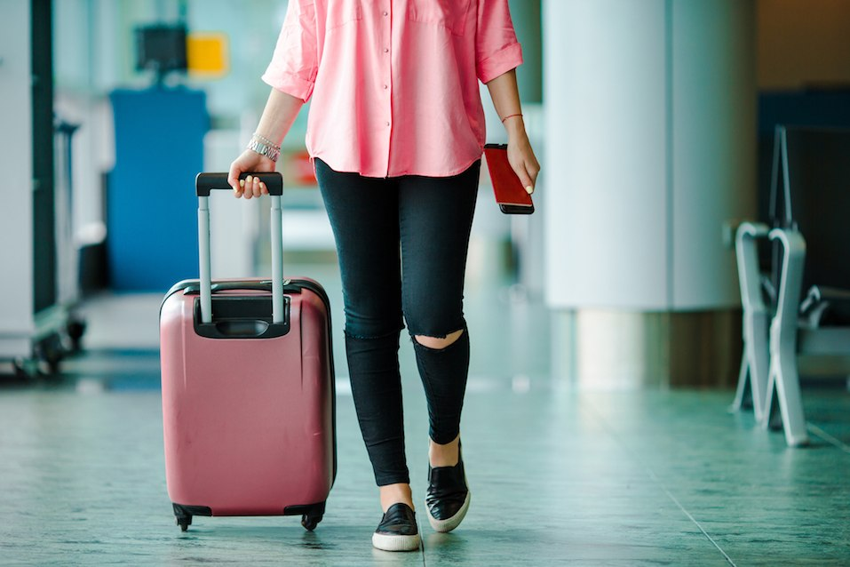 Passenger with passports and boarding pass and pink baggage