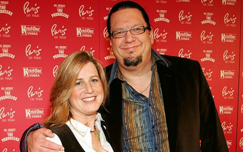 Penn Jillette has his arm around Emily on the red carpet.