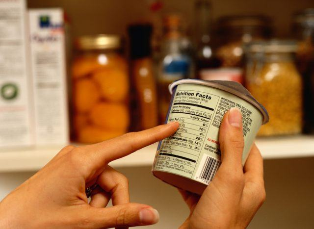 A person reads a nutrition label on a yogurt.