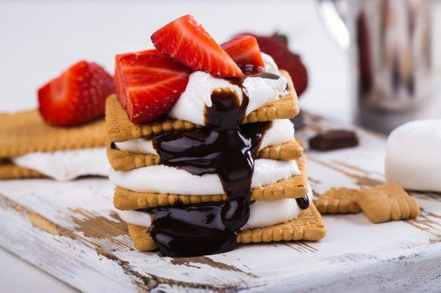 S'mores and strawberries on a wooden table.