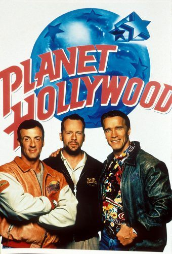 """Bruce Willis, Sylvester Stallone, and Arnold Schwarzenegger pose with a """"Planet Hollywood"""" poster"""