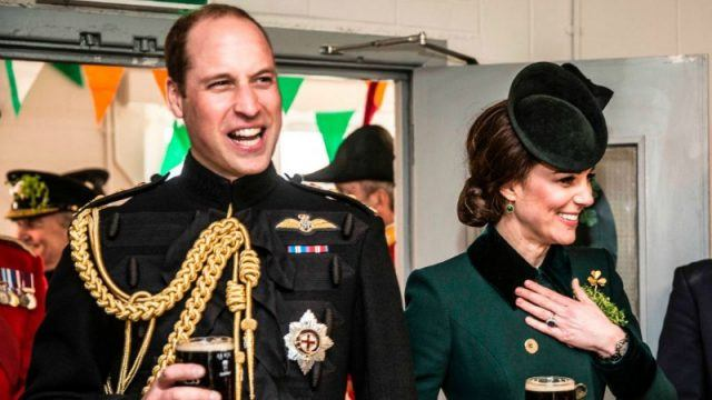 Prince William and Duchess Kate Middleton are standing next to each other holding beers and smiling.