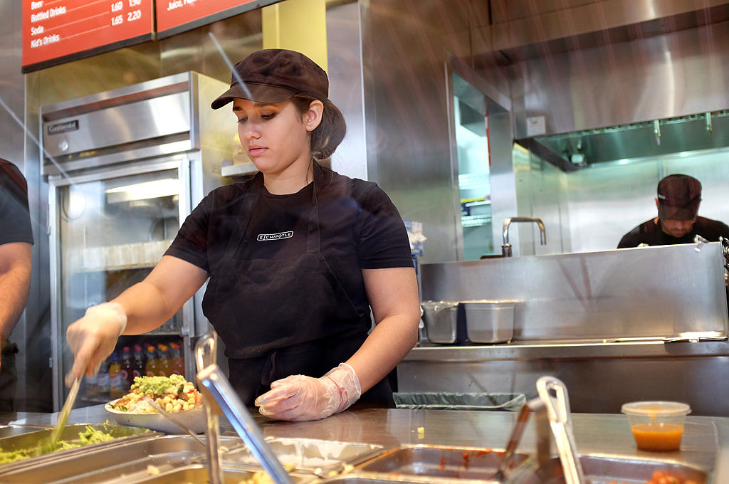 A restaurant worker uses a spoon to get Guacamole